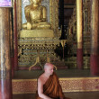 Monk sitting near statue of Buddha, Jumping cat Monastery, Inle lake, Shstate, Myanmar, Southeast Asia — Zdjęcie stockowe #11809110