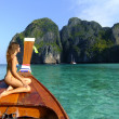 Stock Photo: Young woman in bikini sitting on a stern of longtail boat, Phi Phi Lei island, Thailand