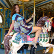 Young woman on merry-go-round carousel — Stock Photo