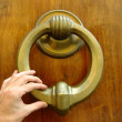 Hand holding doorknocker - Stock Photo