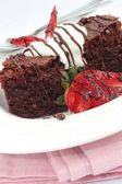 Chocolate brownies with cream and strawberries — Stock Photo