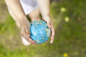 Holding an earth globe in hands — Stock Photo
