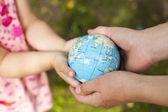 Four hands, holding the globe — Stock Photo