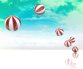 Six jumping white red striped inflatable balls on green blue cloudy sky — Stock Photo