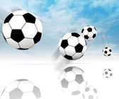 Four football balls on clear spacious field with blue sky — Stock Photo