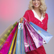 Blond woman with bags smiling - Stock Photo