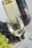Glasses of white and red wine and grapes — Stock Photo