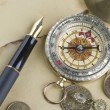 Gold pen with compass and coins — Stock Photo