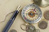 Złote pióro z kompasem i monety — Zdjęcie stockowe