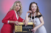 Closeup of two attractive happy girls with retro radio — Stock Photo