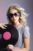 Emotional blonde in headphones with vinyl record — Stockfoto