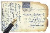 Goldenen kugelschreiber auf retro-postkarte — Stockfoto