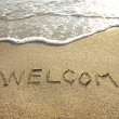 Welcome drawn in the sand with seafoam and wave — Stock Photo #11956940