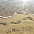 Welcome drawn in the sand with seafoam and wave — Stock Photo