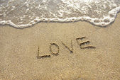 Love drawn in the sand with seafoam and wave — Stock Photo