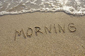 Morning drawn in the sand with seafoam and wave — Stock Photo