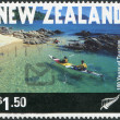 NEW ZEALAND - CIRCA 1999: Postage stamps printed in New Zealand, is dedicated to the 100th anniversary of tourism, shows Kayakers in Abel Tasman National Park, circa 1999 - Stock Photo