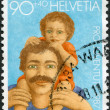 SWITZERLAND - CIRCA 1987: A stamp printed in Switzerland, shows a father and child, circa 1987. Surtax for national youth welfare projects and the Pro Juventute Foundation. - Stock Photo
