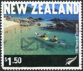 NEW ZEALAND - CIRCA 1999: Postage stamps printed in New Zealand, is dedicated to the 100th anniversary of tourism, shows Kayakers in Abel Tasman National Park, circa 1999 — Stock Photo