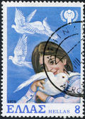 řecko - cca 1979: razítka vytištěné v řecku, je věnována mezinárodní rok dítěte, líčí dívka a holubi a emblém, cca 1979 — Stock fotografie