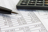 Calculator and pen on financial papers — Stock Photo