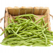 Bunch of green beans coming out of a wooden basket — Stock Photo