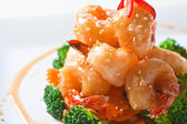 Battered king prawns on a bed of steamed broccoli — Stock Photo