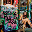 Young caucasian woman in front of graffiti tram — Stock Photo #12330881