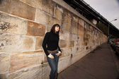 Young woman leaning against a sandstone wall — Stock Photo