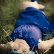Beauty in blue dress lying in the grass — Stock Photo #11978964