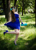 Beauty in blue dress lying in the grass — Stock Photo