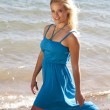 Woman blue dress beach smile - Stockfoto