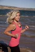 Woman run by water pink tank — Stock Photo
