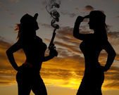 Two women silhouette one gun smoke — Stock Photo