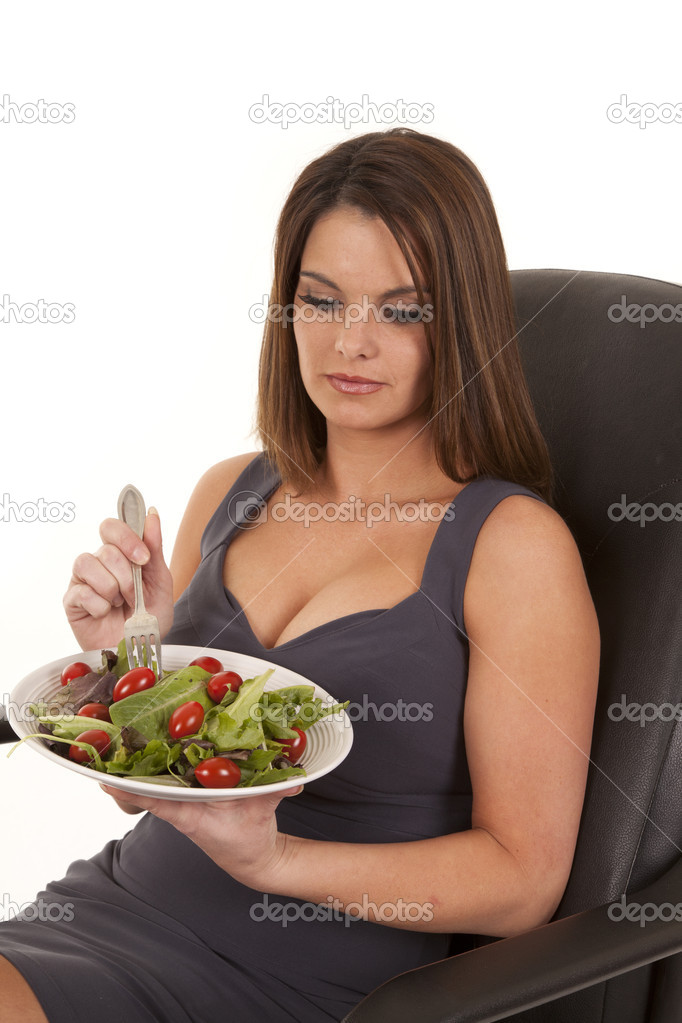 A woman sitting in her chair digging into her salad with her fork  Stock Photo #11949061