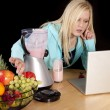 Woman laptop making smoothie — Stock Photo