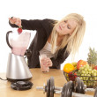 Woman putting strawberry in blender — Stock Photo