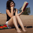 Woman reading by water — Stock Photo