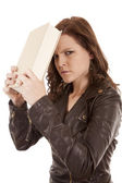 Woman slamming book against head looking — Stock Photo