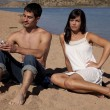 Couple on beach not happy phone — Stock Photo #11971349