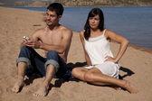Coppia sulla spiaggia di telefono non felice — Foto Stock