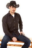Cowboy sitting with gun on leg — Stock Photo