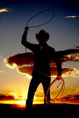 Cowboy with rope in air sunset — Stock Photo