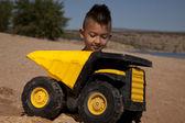 Junge hinter lkw in sand — Stockfoto