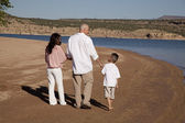 Family beach walk backs — Stock Photo