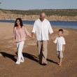 Family walking on beach happy - Stock Photo