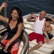 Happy woman driving boat scared boys — Stock Photo