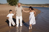 Family wading on beach white — Stock Photo