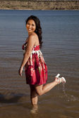 Woman red dress foot up water — Stock Photo