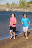 Girls running on beach — Stock Photo